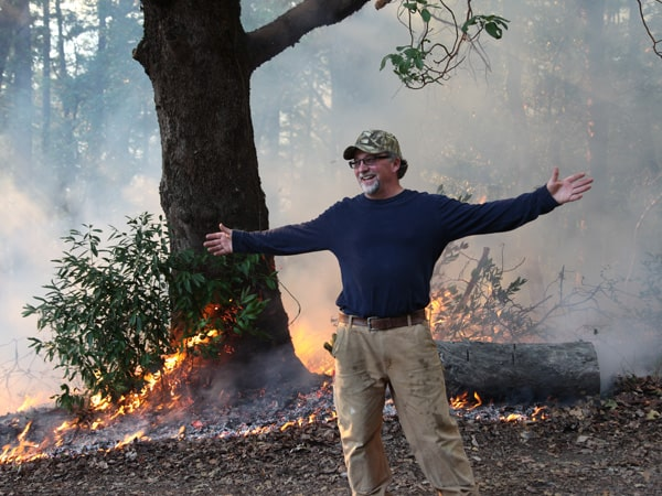 A happy landowner shows off the controlled burn being implemented on his property as part of a TREX training exchange. Photo by Larry Luckham.