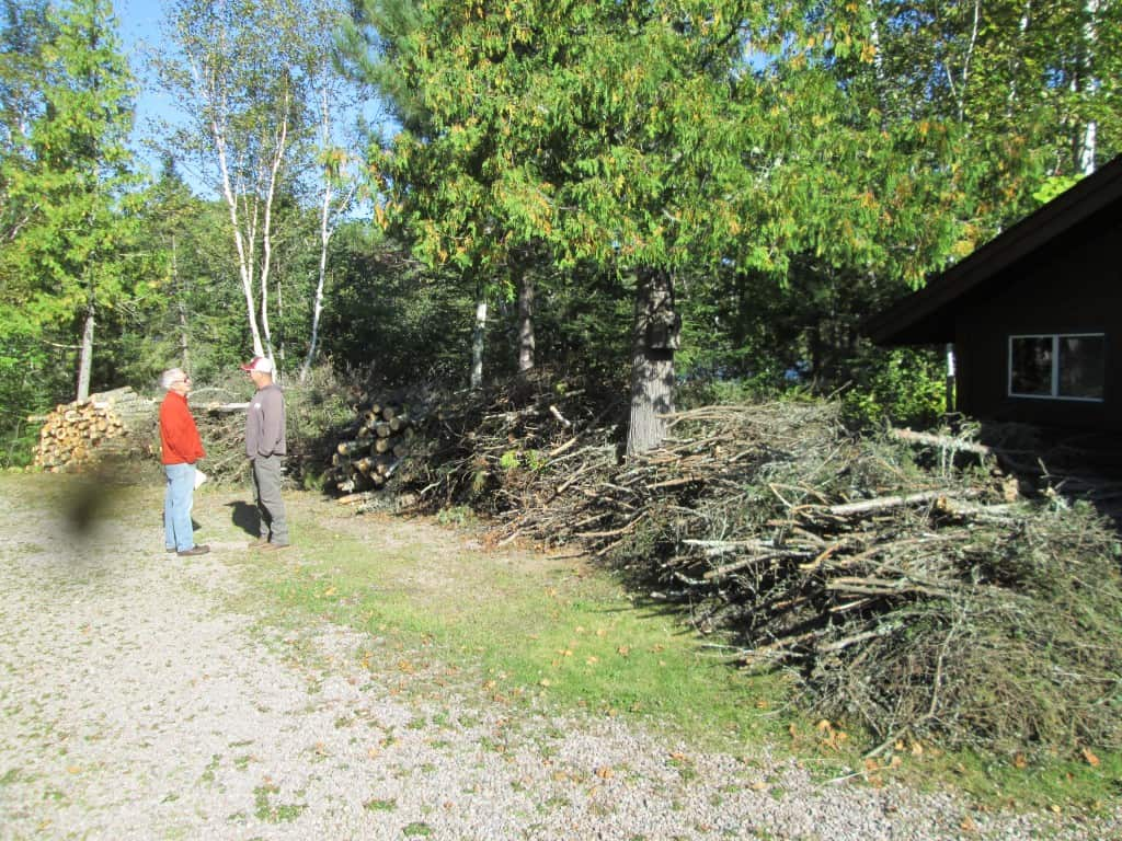 Charlie Ragan (left) and his wife are seasonal residents who hired a local college student to cut and pile all of this slash in order to reduce fuel levels and improve ingress/egress on their property. Photo credit: Gloria Erickson.