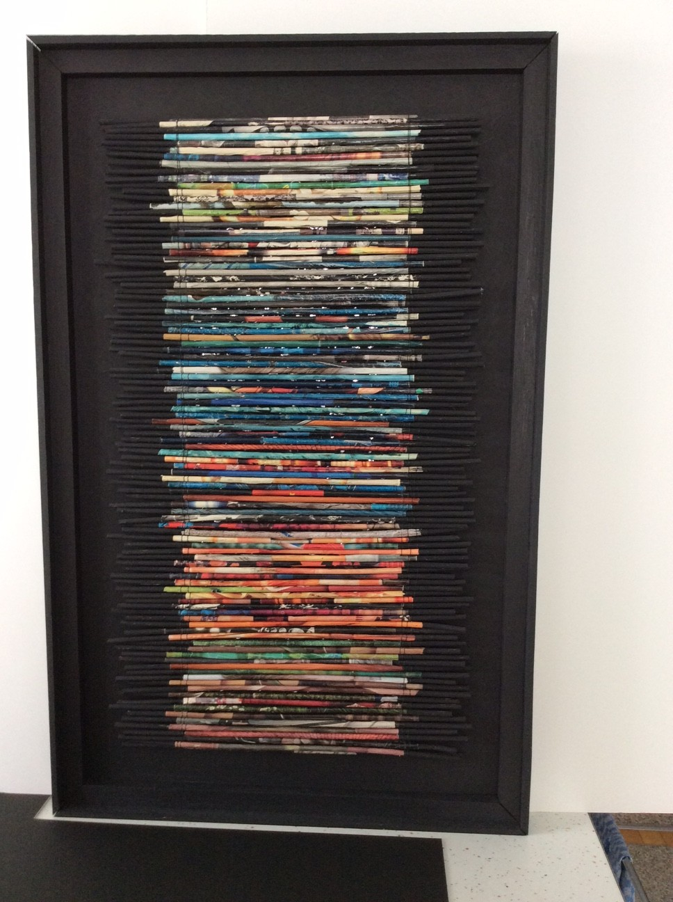 "A piece by Margaret ""Muff"" Schumacher. The piece is based on the Finnish weaving style called ""Raanu"". It was created right after the ""Pagami Creek Fire, 2011."" The 100 'charred' sticks represent the 100,000 acres of woodland that was destroyed. Reprinted with artists permission."