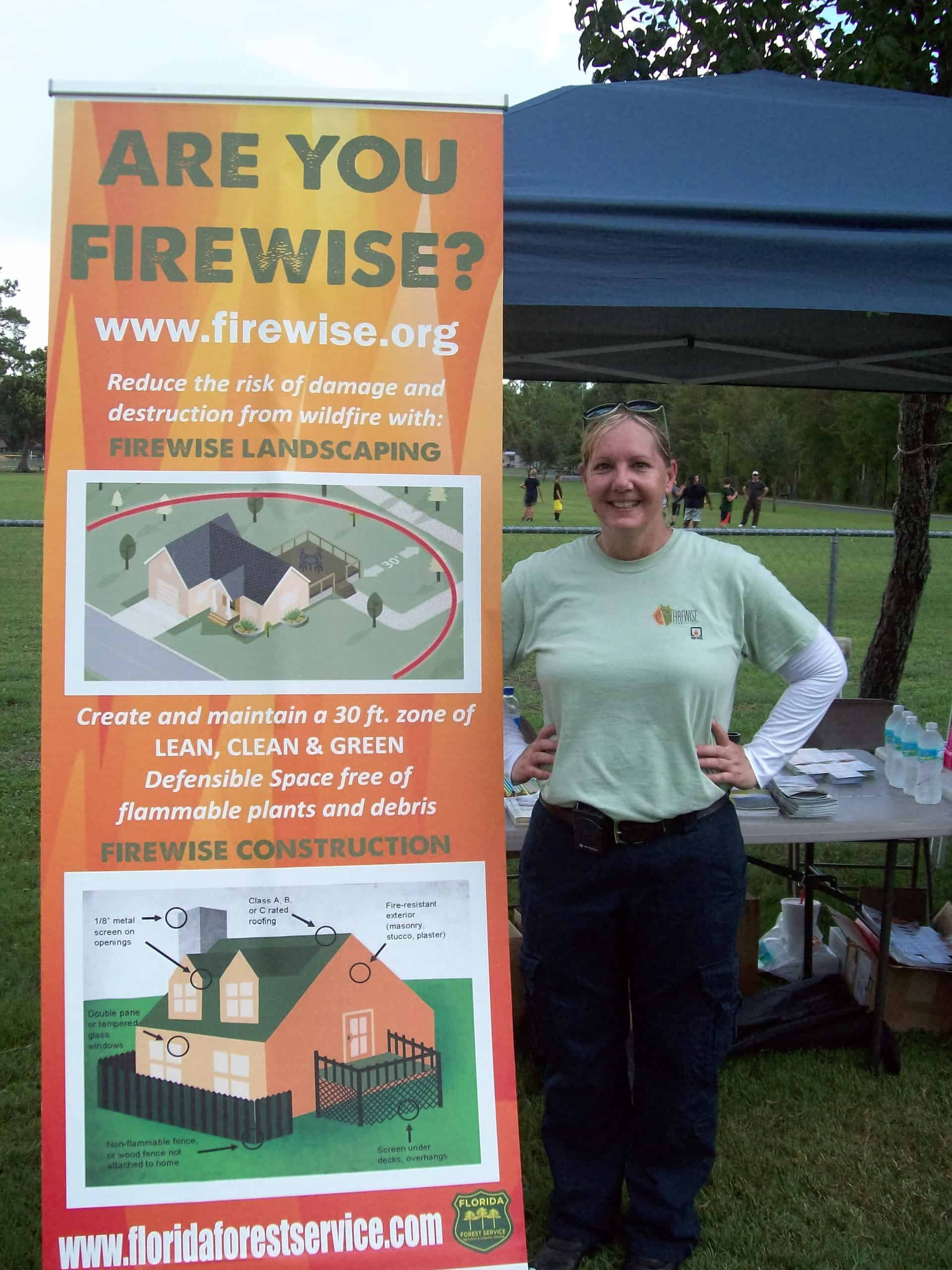 Anderson standing next to a Firewise banner