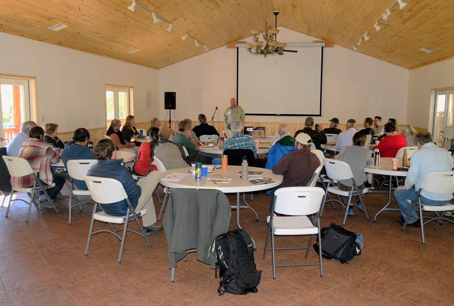 Event attendees listening to a presentation on ponderosa pine and the timber economy
