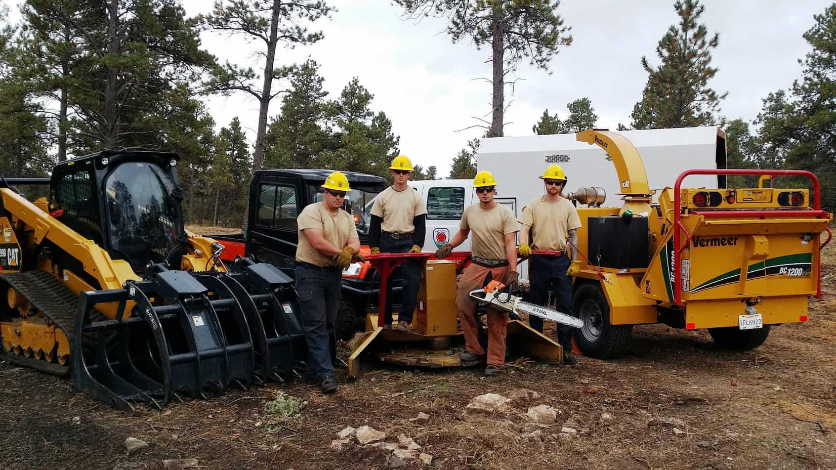 Four members of the mitigation crew (all veterans) pose in front of logging equipment