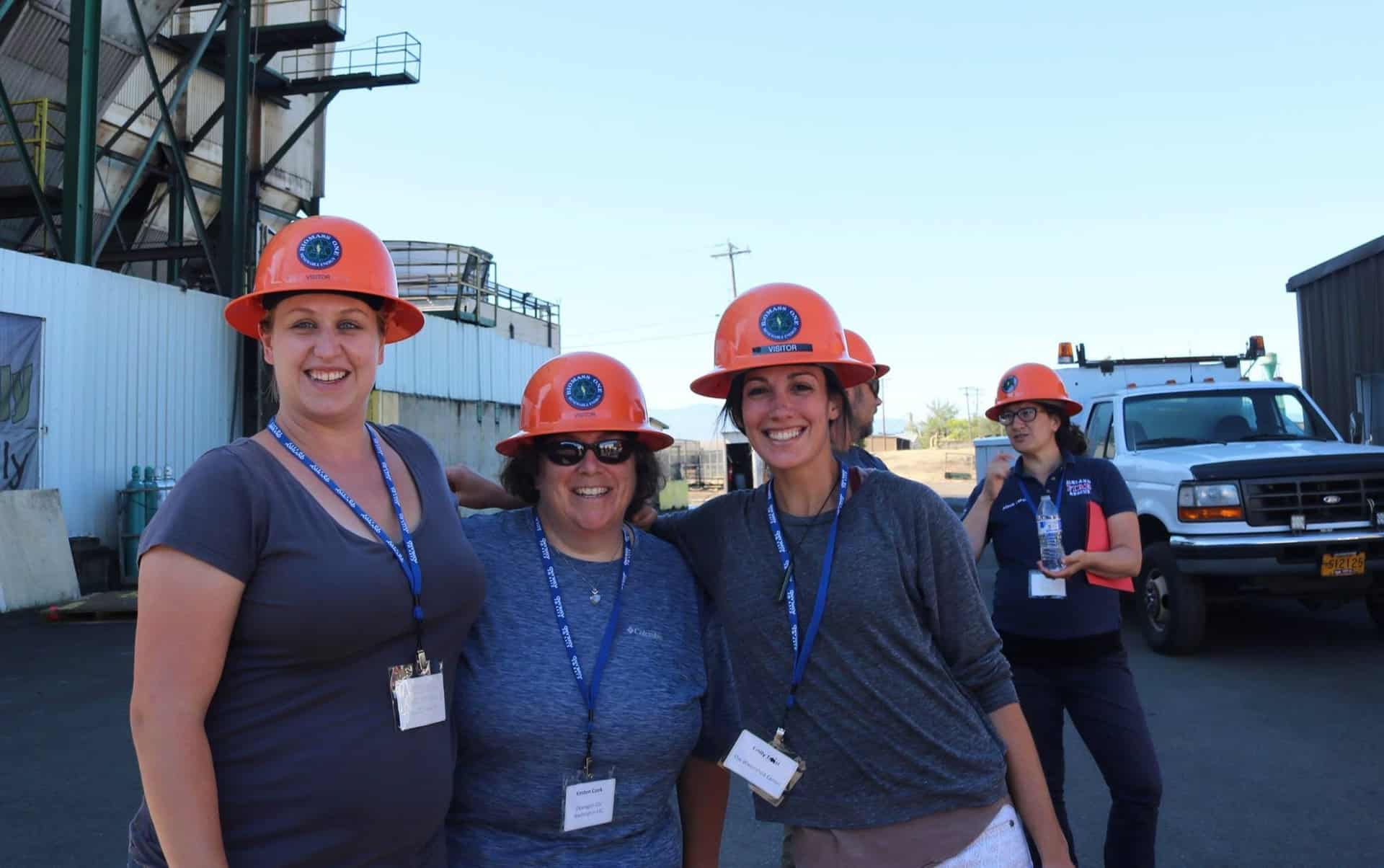 Three participants pose while on a tour of a biomass plant, hardhats and all!