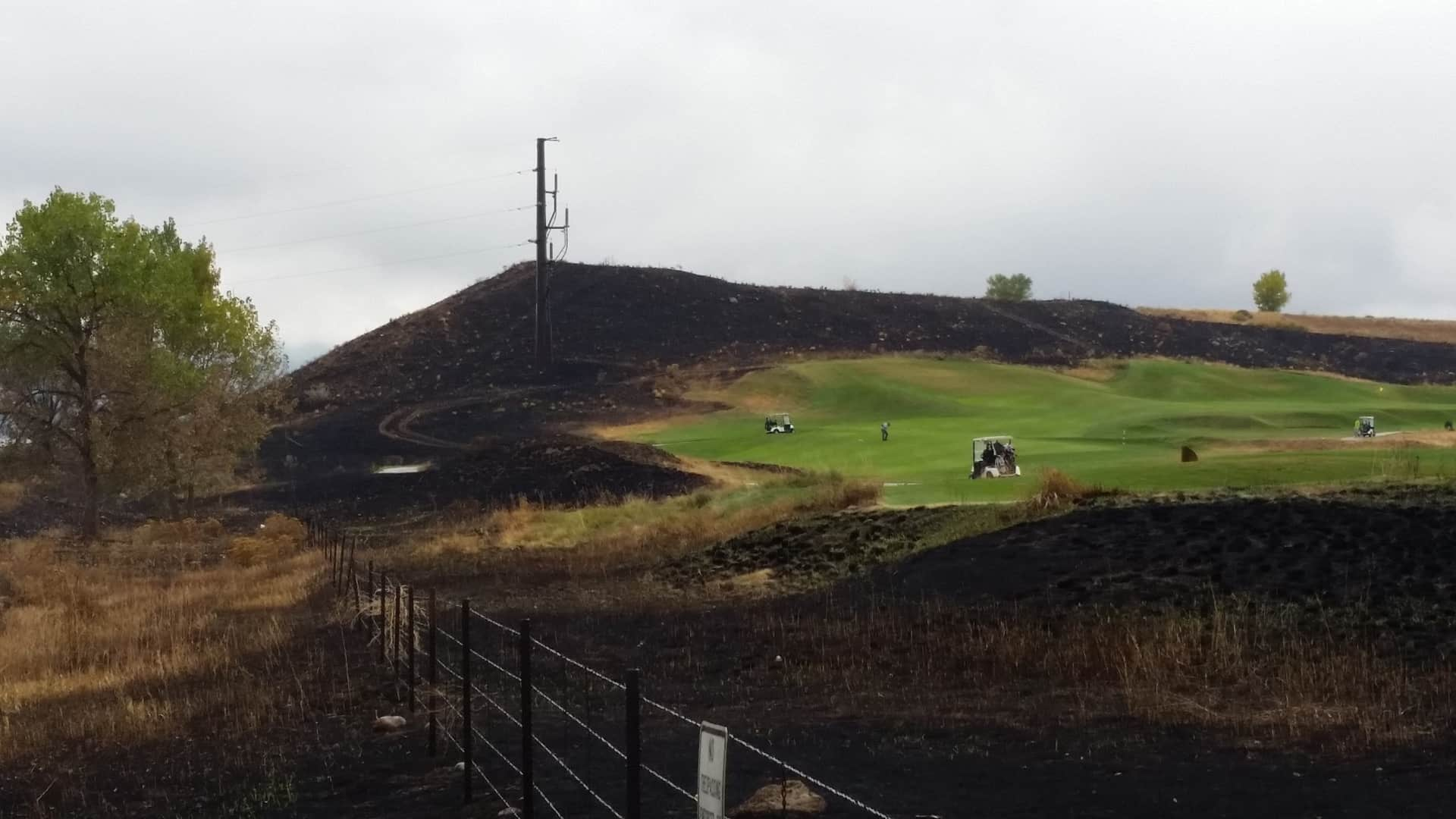 Golf carts travelling on a golf course, the outline of which also marks the boundary of a recent wildfire.