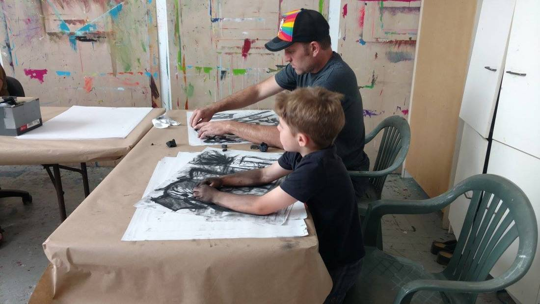 An adult and child making charcoal sketches.