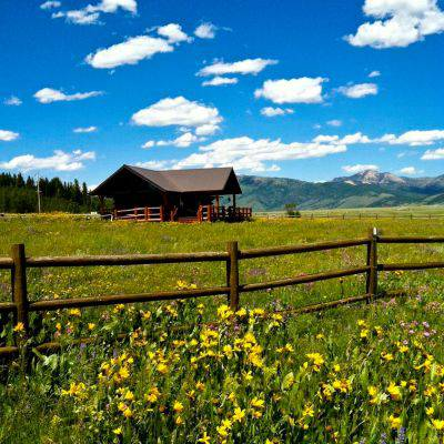 Landscape view of the ranch and the surrounding meadow, covered with wildflowers.