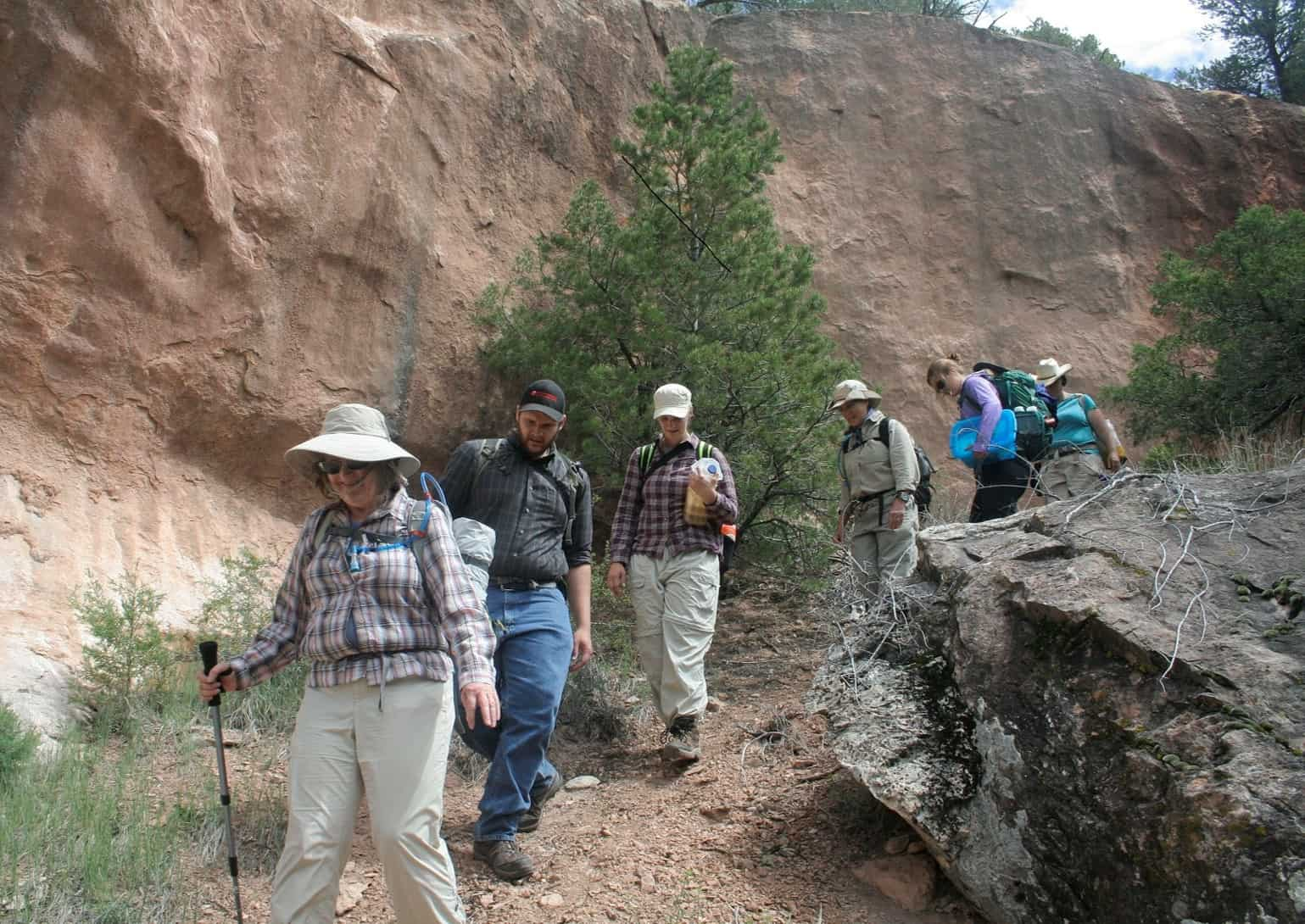 Six adults hiking through through the Zuni mountain landscape.