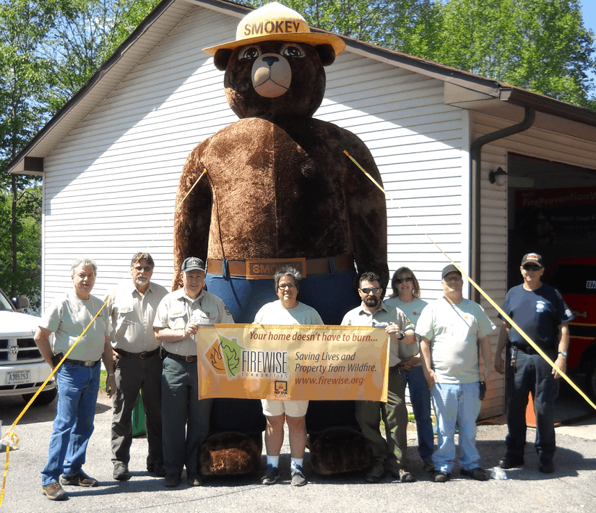 FAC partners posing with a Firewise banner and an inflated Smokey Bear; Firewise is an important component of Southeast FAC efforts, like in most places.