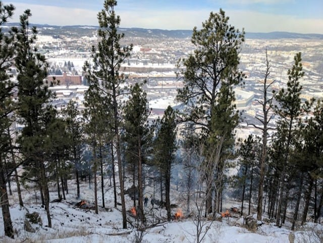 Piles burning in a snow-covered forest, with Rapid City in the background