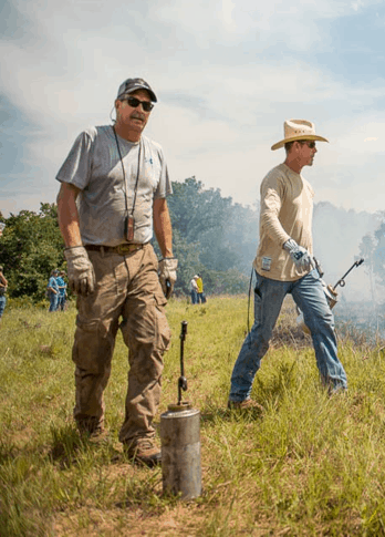 Two ranchers with drip torches in a field