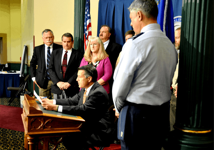 Governor Sandoval reading the proclamation, with various agency officials beside him
