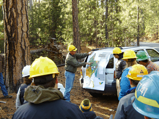 A group of people, equipped with hardhats, looking at a map in the field.