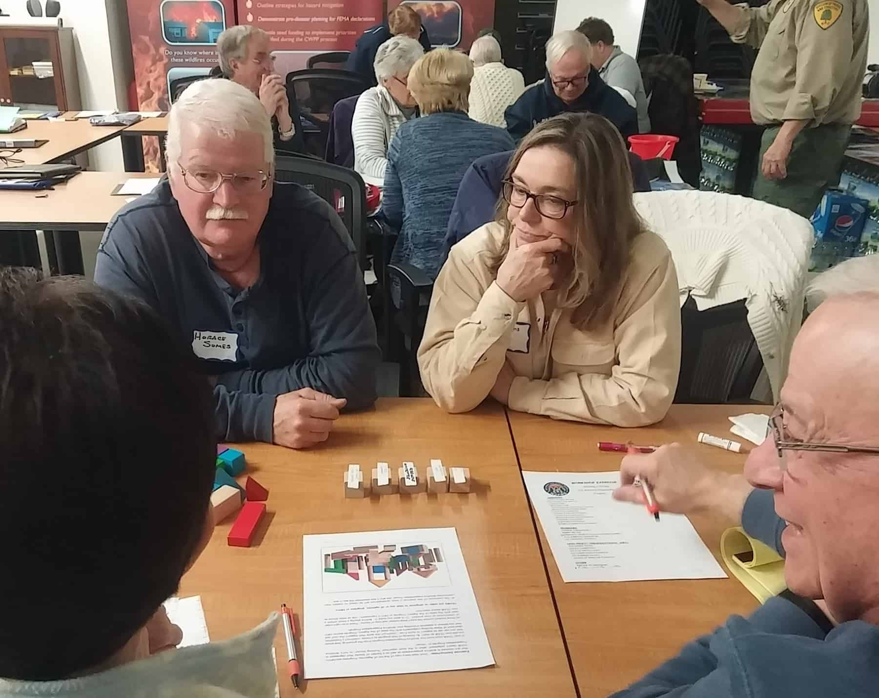 Small groups work through wildfire preparedness plan exercise with building blocks.