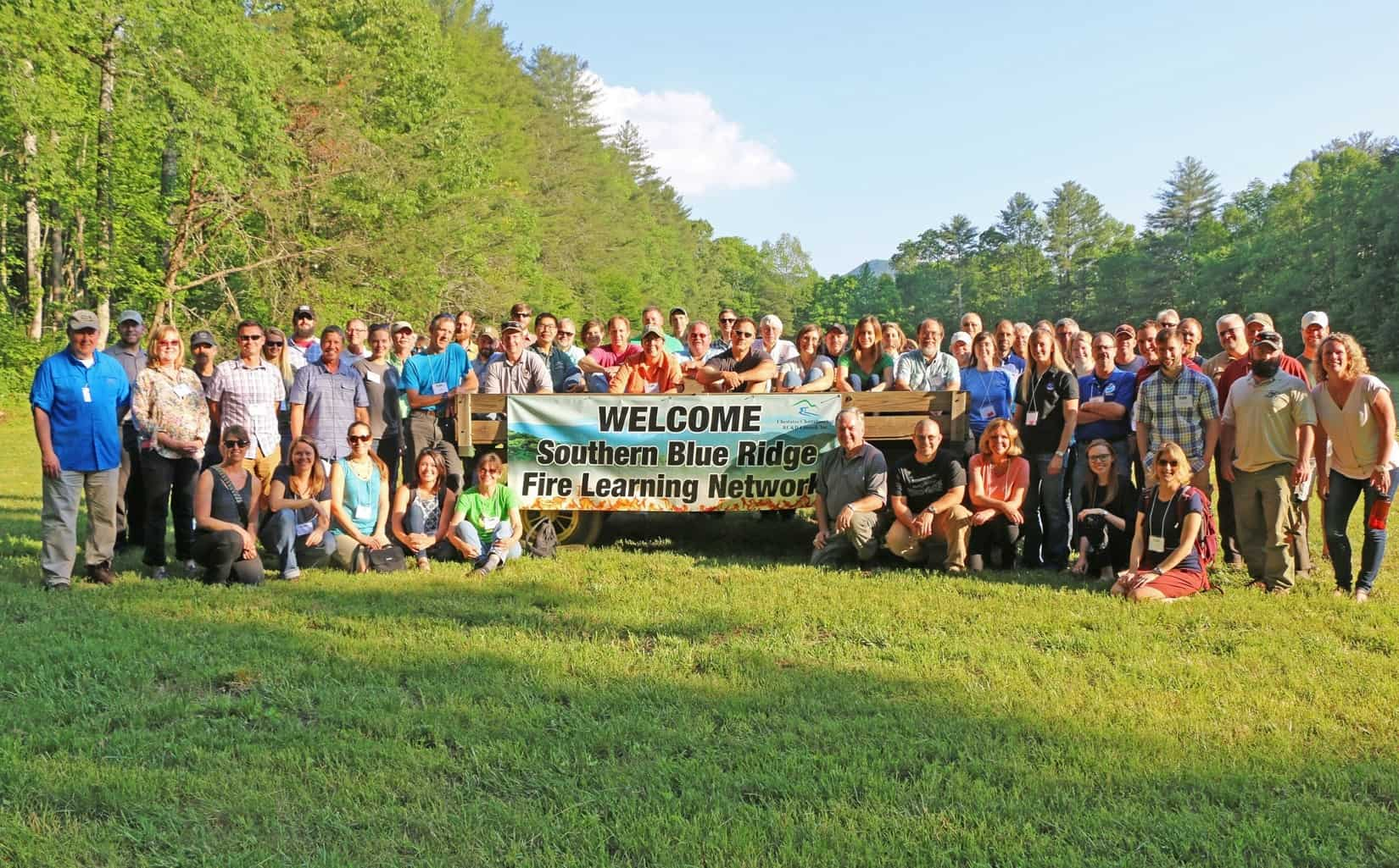 Southern Blue Ridge Fire Learning Network workshop attendees taking a break from talking about wildfire adaption to enjoy a farm-fresh dinner (group posing by welcome sign)