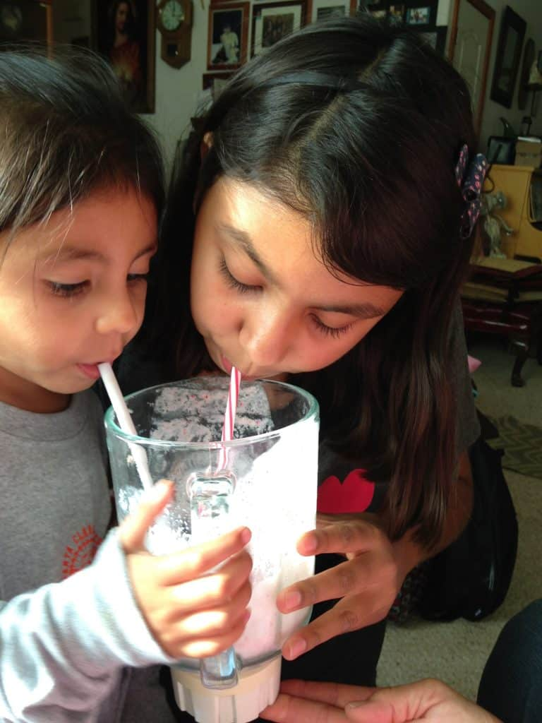 Porfirio's two daughters sharing a milkshake from the blender.