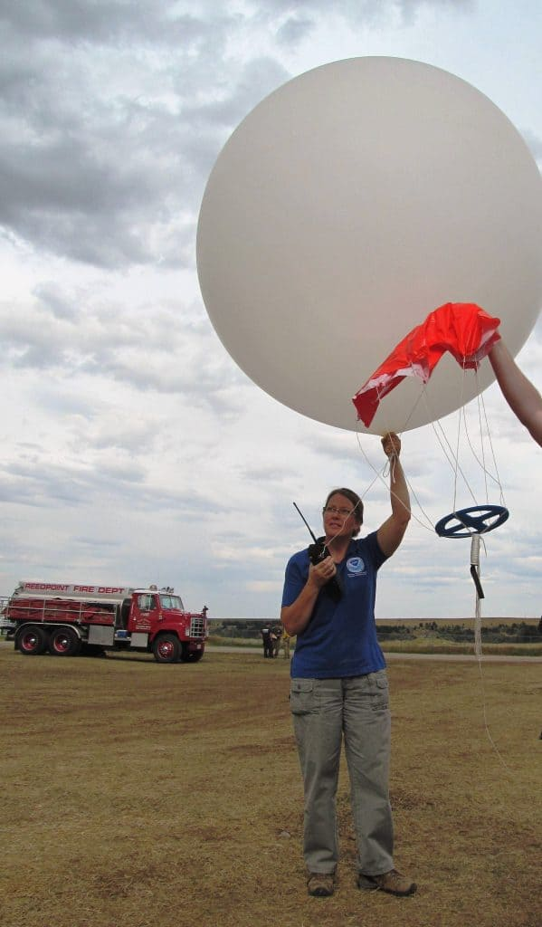 Coleen holding a weather balloon.