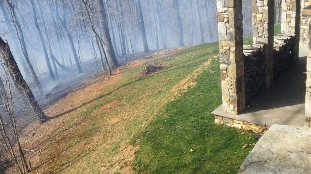 "Smoke carrying through the trees near a home. There is a buffer (""defensible space"") between the home and its surrounding forest."