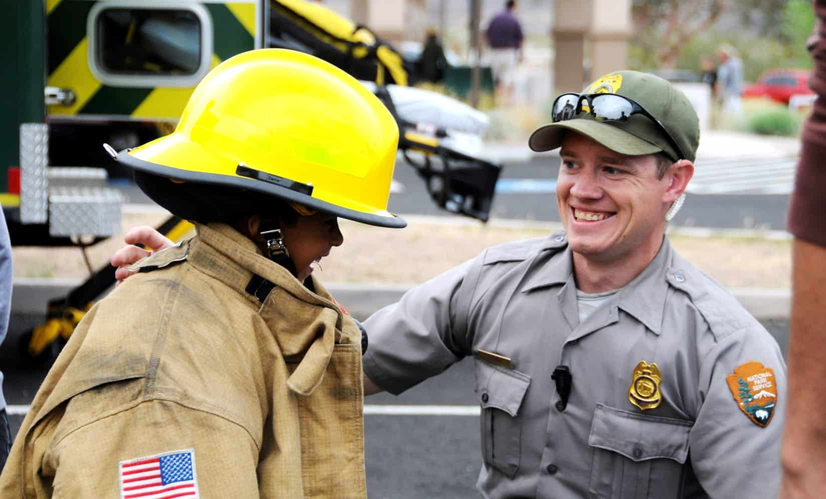 A ranger with a student who is happily testing out a wildland firefighting uniform