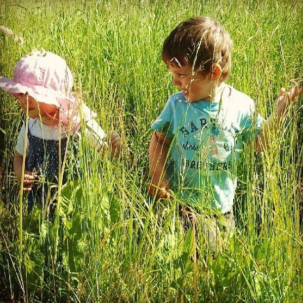 Two kids playing in tall grass