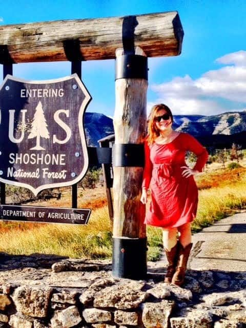 Kristin standing next to the Showshone National Forest welcome sign