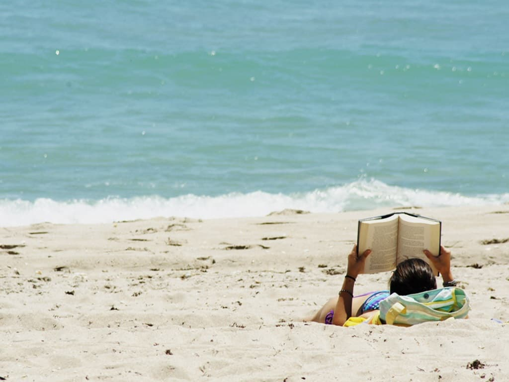 Woman reading a book by the ocean