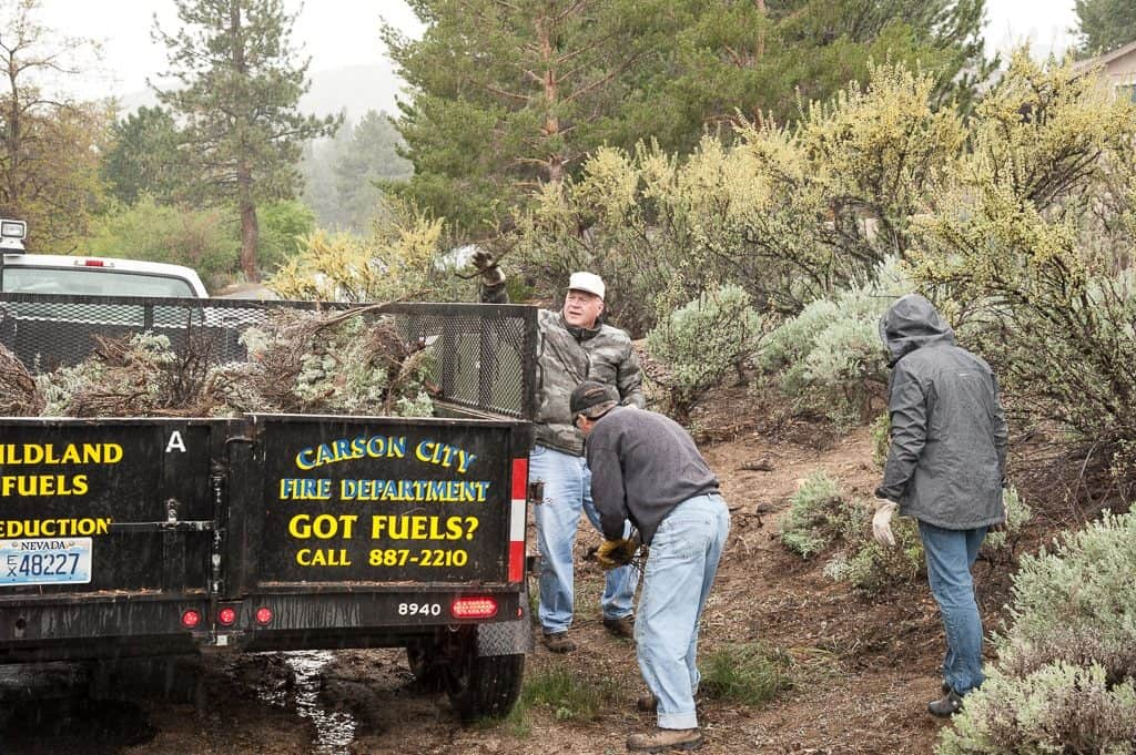 Residents loading forest debris into a trailer