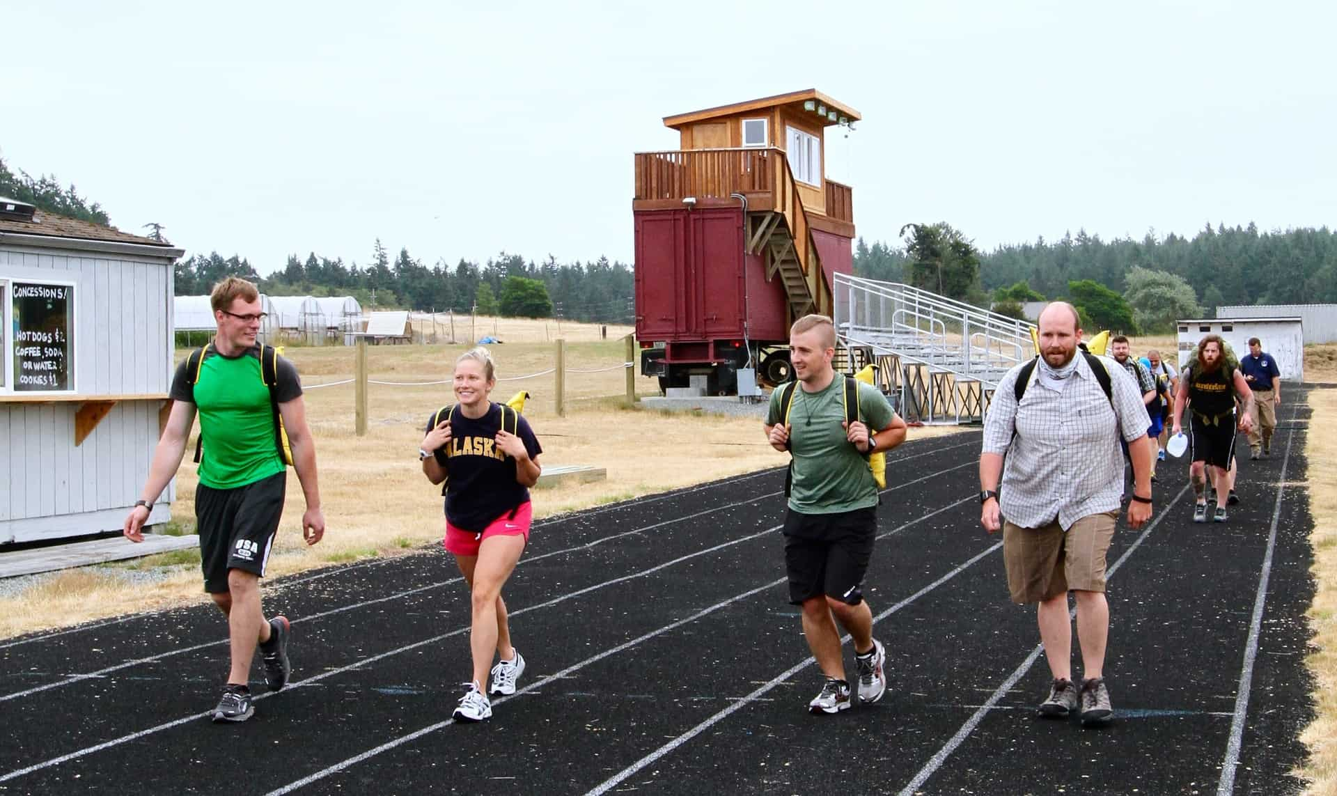 Pack test participants walking around a track, carrying backpacks