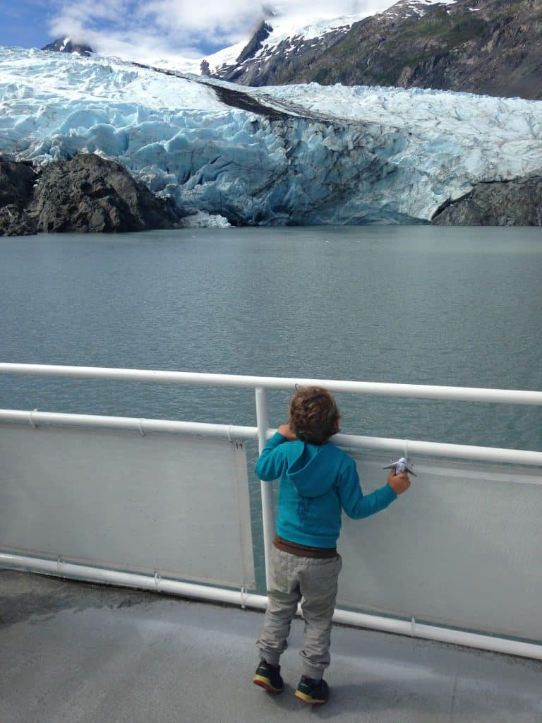 Toddler observing a glacier from the deck of a boat