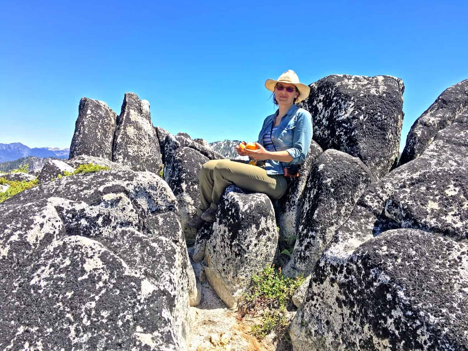 Karuna sitting on a rock outcropping, overlooking the Duck Lakes in the 'Miracle Mile' of the Russian Wilderness