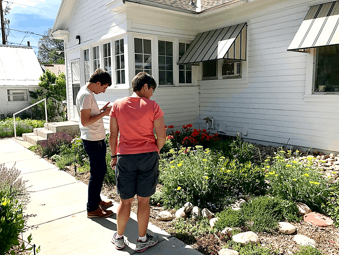 Two participants examine a building's outdoor lanscaping