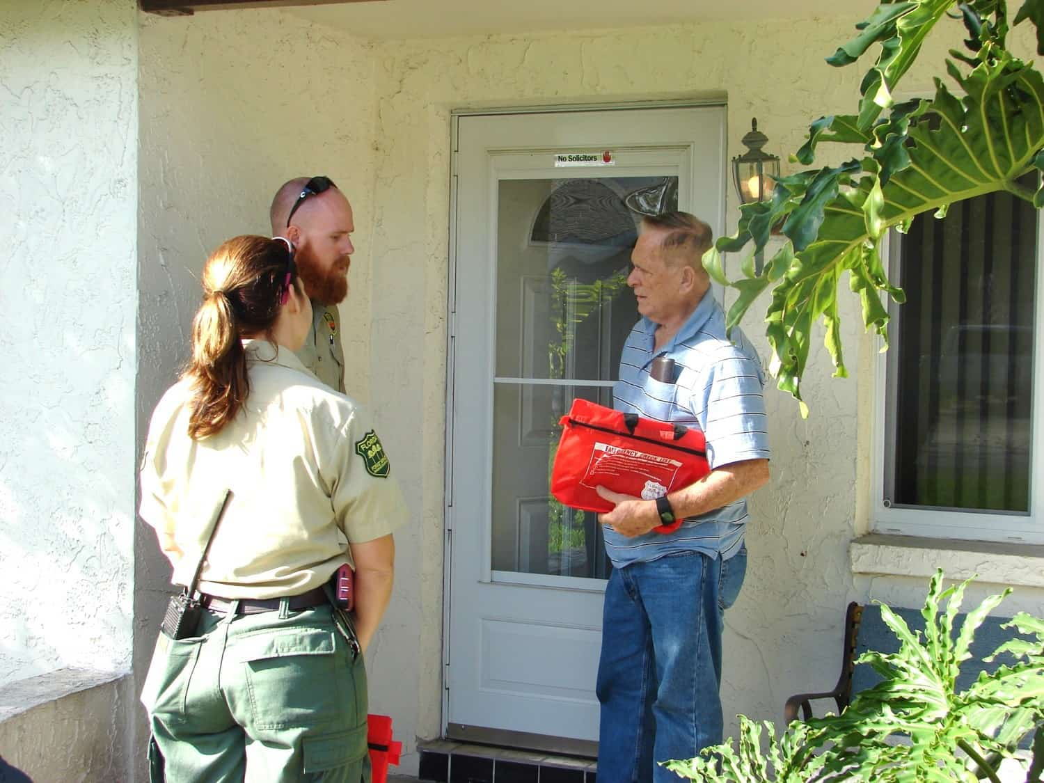 Two rangers talking with a homeowner on his porch