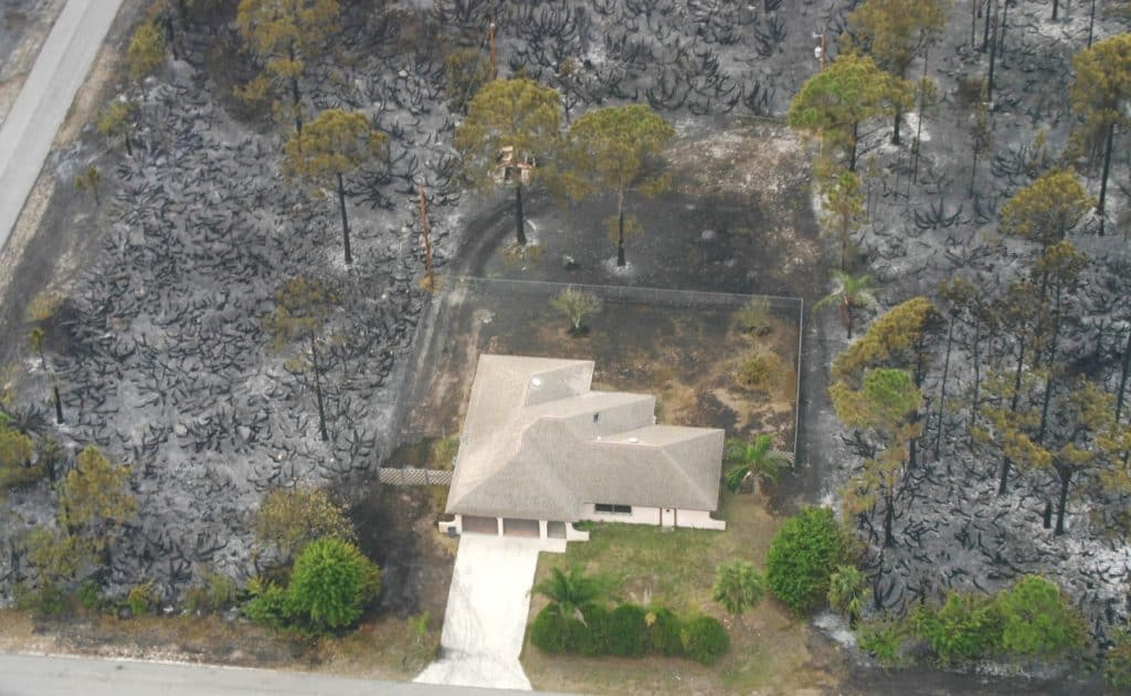 Areal view of standing home, surrounded by a buffer and then burnt vegetation; Florida Forest Service's wildfire risk mapping and local outreach play a role in reducing residential wildfire risk as well
