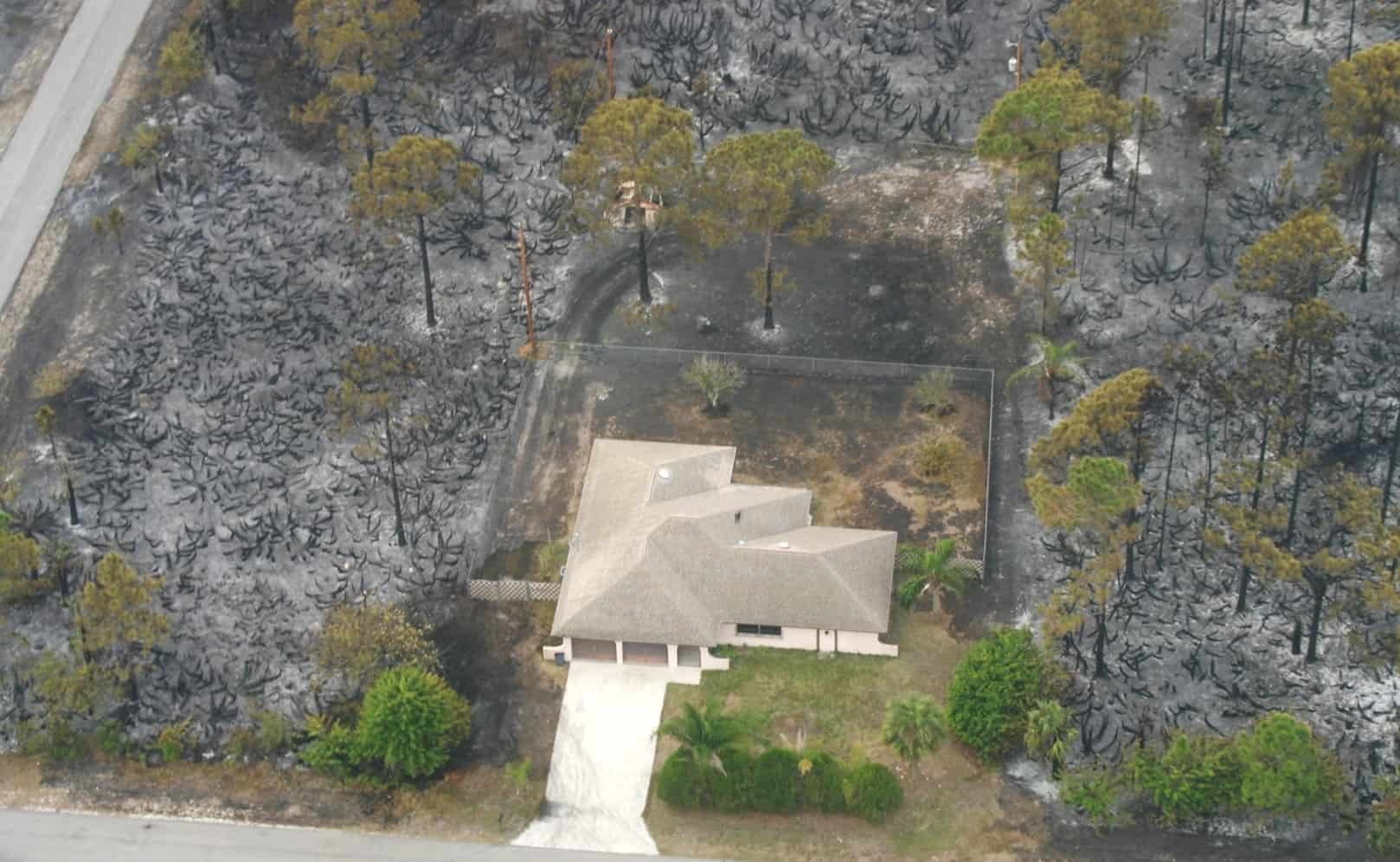 Aerial view of a home buffered by defensible space but otherwise surrounded by a burned landscape