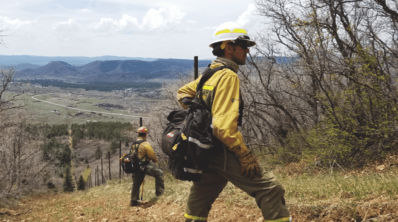 Photo of two prescribed fire practitioners with a community in the background
