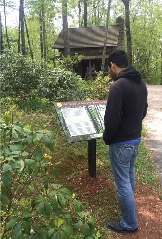 Visitor reading a Fire Learning Trail interpretive sign