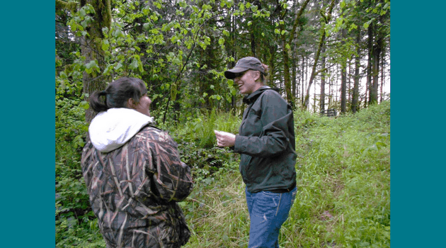 Alison talking with a landowner in the forest