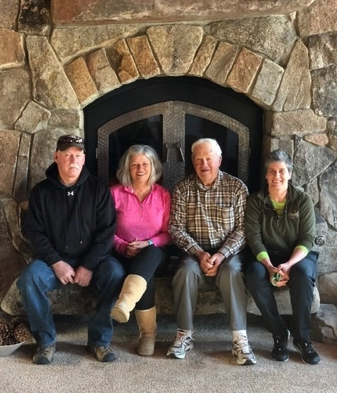 Lynn and her family sitting by a fireplace