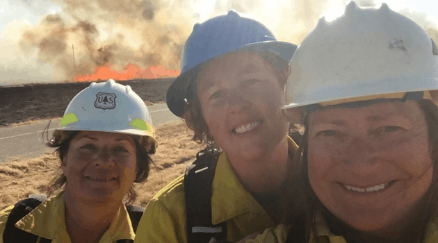 Jean, Lynn and Kelly, with a prescribed fire in the background, at WTREX 2018 where they talked about leadership in fire