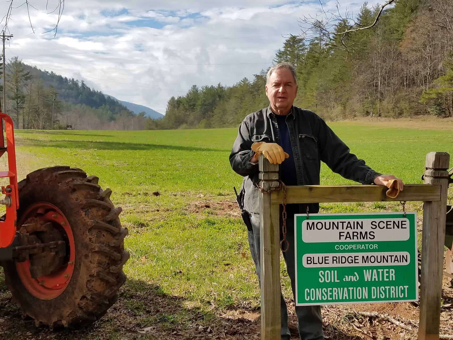 Frank standing next to a tractor and a sign indicating that his farm, Mountain Scenes Farm, is a cooperator with the Blue Ridge Mountains Soil and Water Conservation District