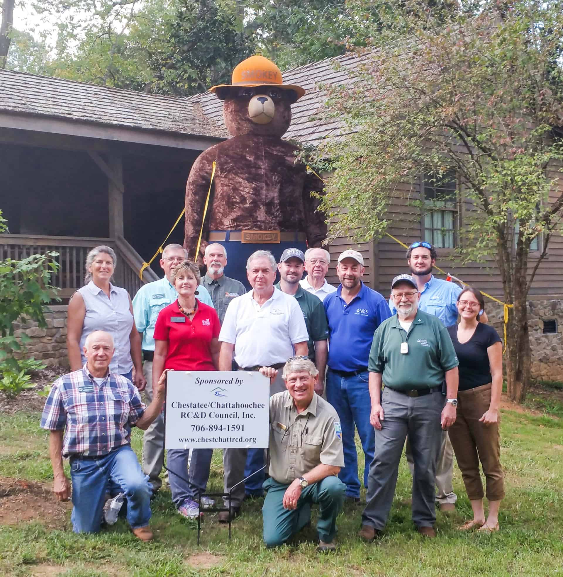 Frank and 12 colleagues with a Smokey the Bear prop