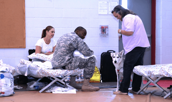 Three people, one of whom is in a military uniform, talking in an evacuation shelter