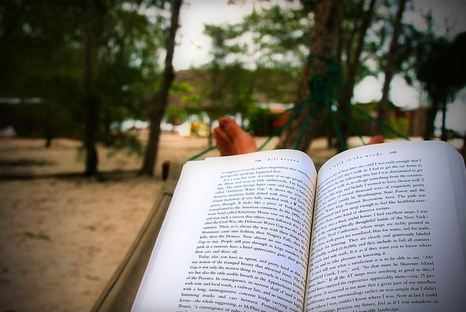 A person holding a book while in a hammock, overlooking a sandy landscape. Check out our summer reading list!