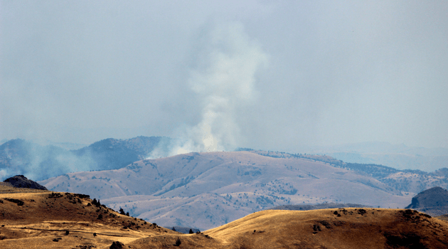 Smoke plume off in the distance, over a range landscape