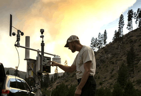An air resource advisor adjusting smoke monitoring equipment