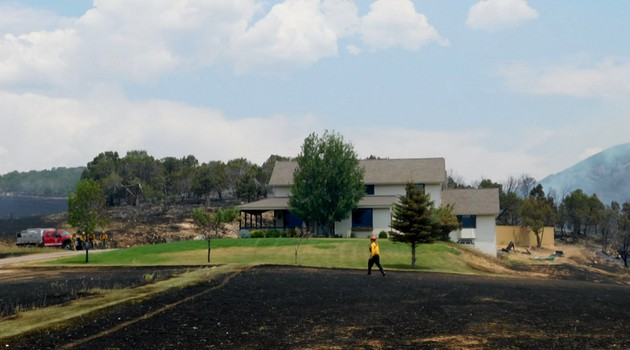 Firefighter and FAC Net member Eric Lovgren walking across a burnt field, with an unharmed home in the background