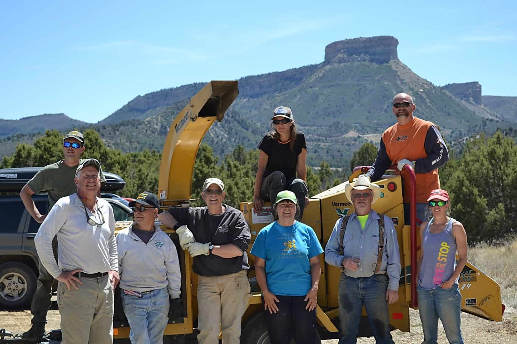 Group of volunteer pause for a photo in front of a wood chipper