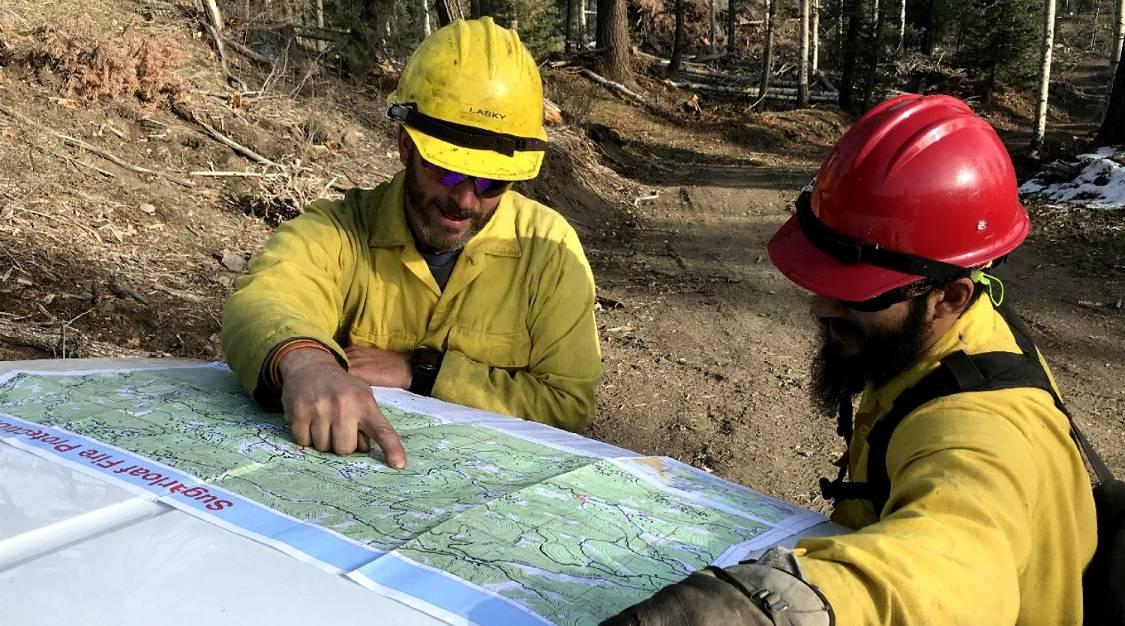 Two firefighters discussing a map laid over the hood of a truck