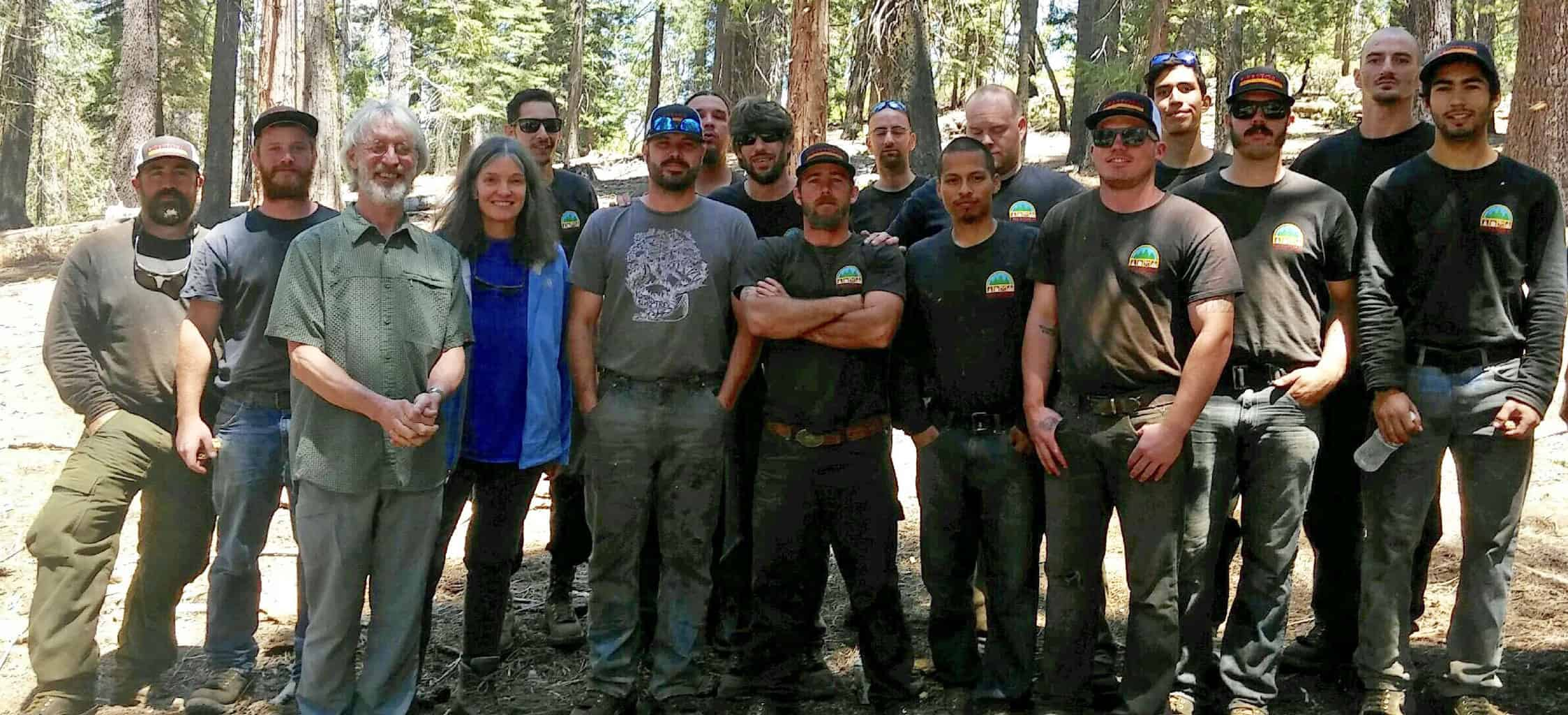 Kimberley and John with 16 Firestorm crew members, with trees in the background