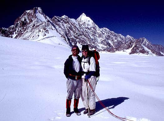 Kimberley and John in mountaineering gear with a snowy, mountainous backdrop