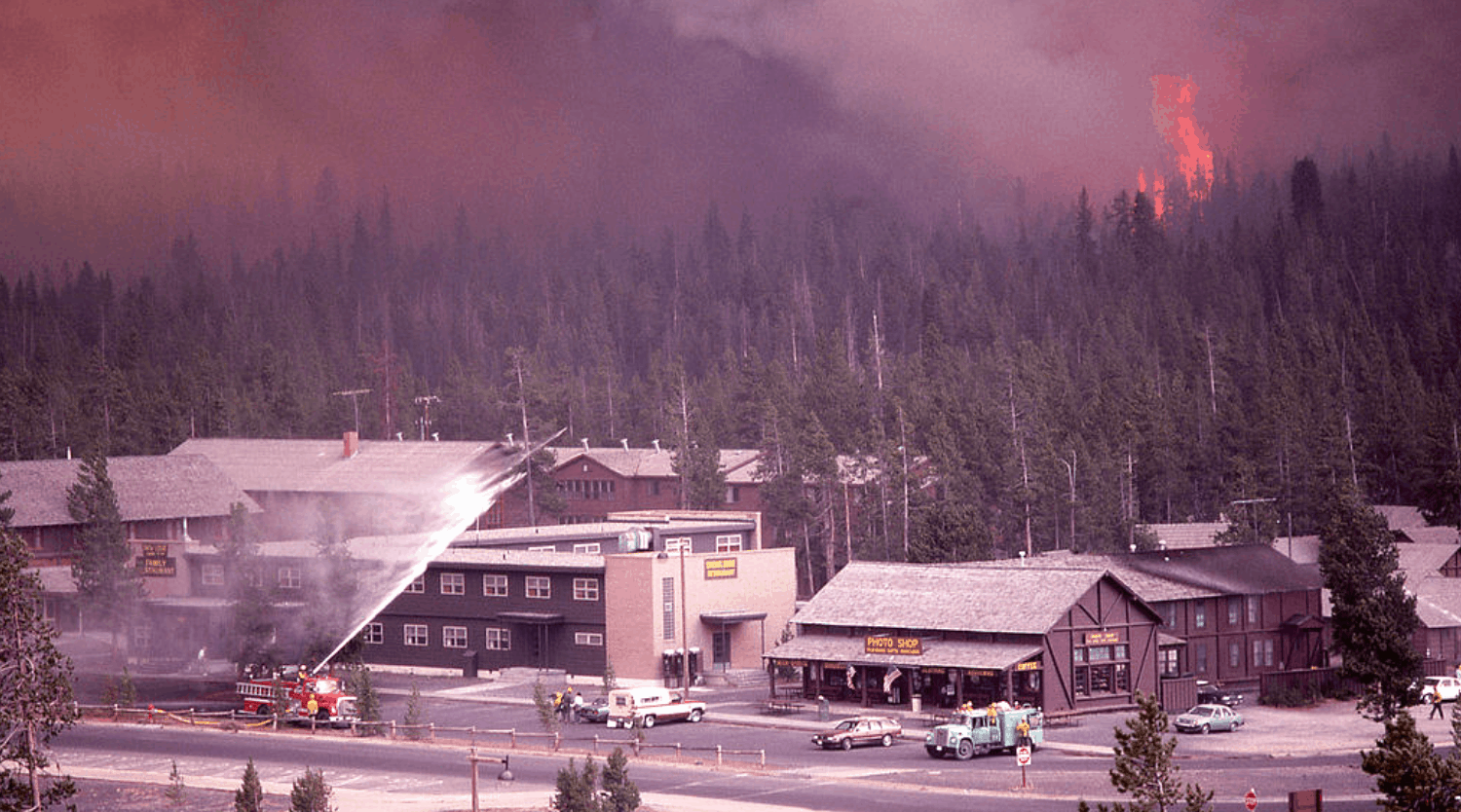 Flames approaching the Old Faithful Lodg, with water being sprayed in the foreground